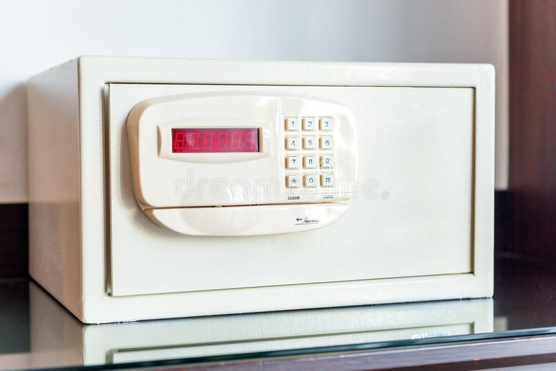 Vitt litet kassaskåp med det kodade låset på tabellen i hotellet royaltyfri bild