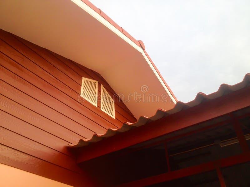 Vitt lufthålfönster i brunt hus royaltyfri foto