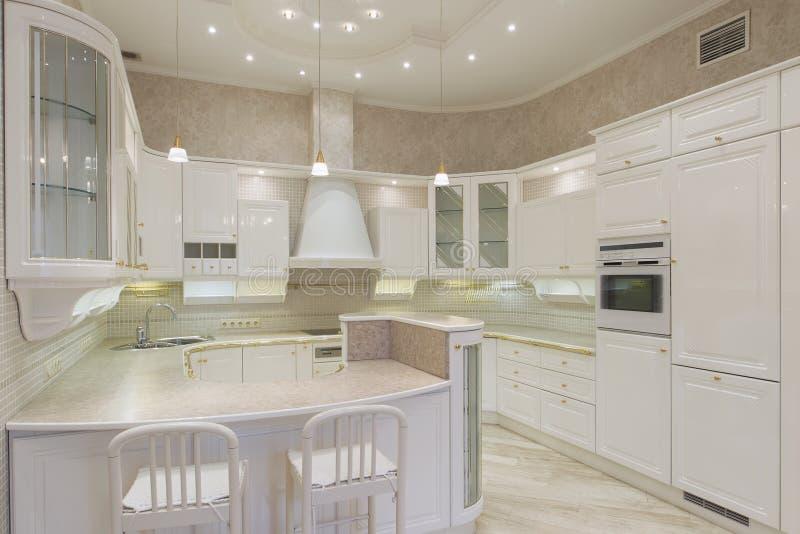 Vitt lyxigt kök i ett modernt hem fotografering för bildbyråer
