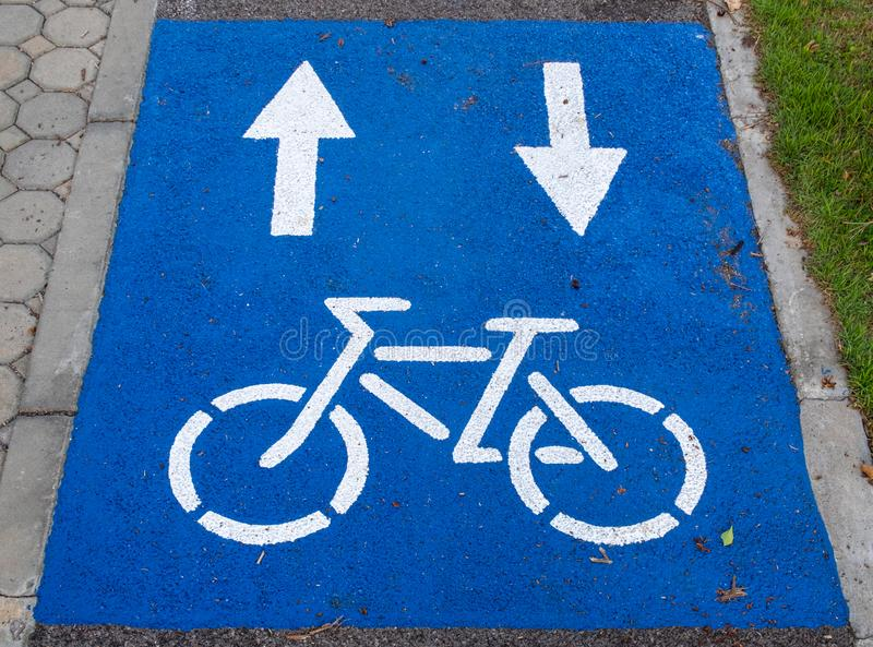 Vitt målat cykeltecken på blå bakgrund royaltyfria bilder