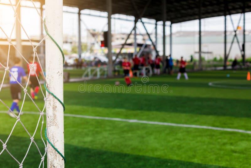 Vitt målstolpar och ingrepp av målet med oskarpa fotbollsspelare royaltyfria foton