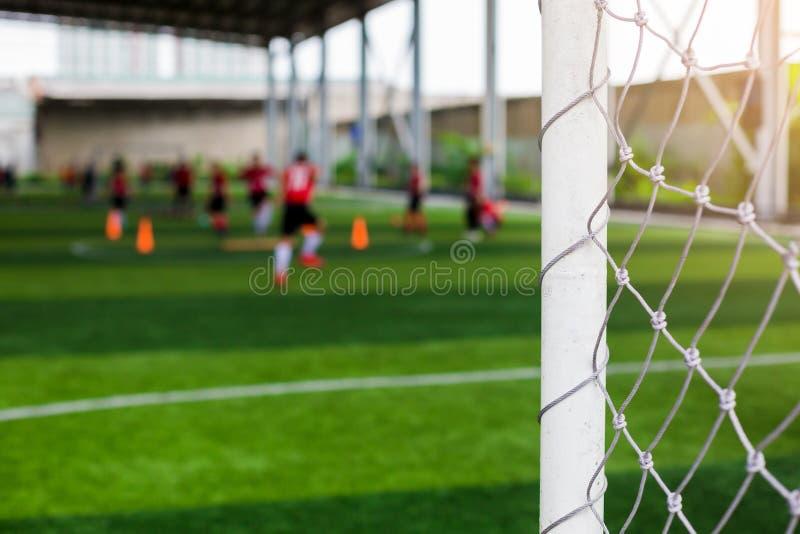 Vitt målstolpar och ingrepp av målet med oskarpa fotbollsspelare arkivbilder
