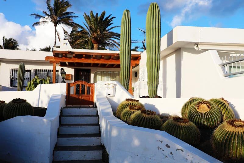 Vitt modernt hus med kaktusvegetation i den Lanzarote ön, Spanien Sommarsemester, loppdestination, hushyrabegrepp royaltyfri bild