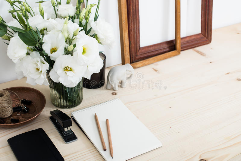 Vitt modernt kvinnligt arbetsskrivbord med blommor royaltyfri bild