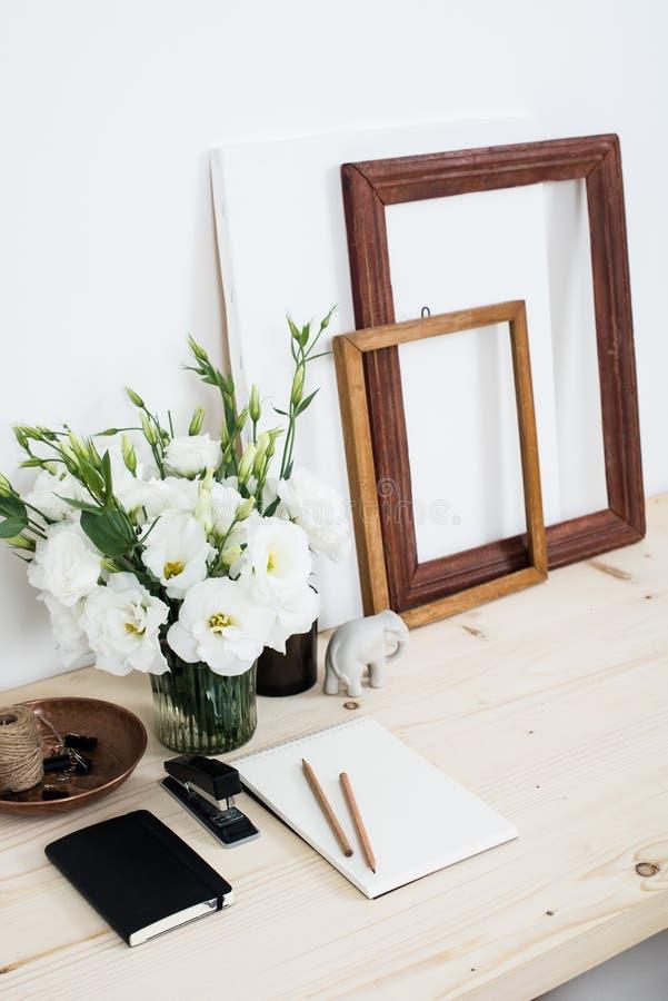 Vitt modernt kvinnligt arbetsskrivbord med blommor arkivbild