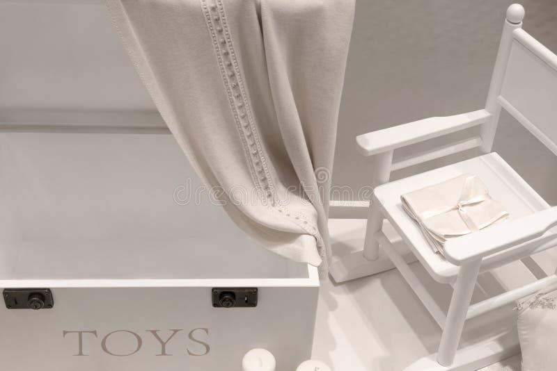 Vitt naturligt trämöblemang i barns rum i form av en enhet och en gungstol arkivbild