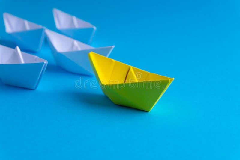 Vitt och gult pappers- fartyg eller skepp i en riktning på blå bakgrund royaltyfri illustrationer