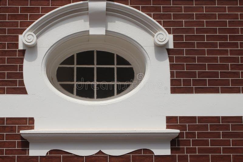 Vitt ovalt fönster med stuckaturen i rubin-färgad tegelstenvägg royaltyfri fotografi