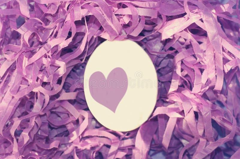 Vitt påskägg med ett ljust - purpurfärgad hjärta på bakgrunden av det purpurfärgade redet av dekorativt purpurfärgat gräs Ägg, kn arkivfoton