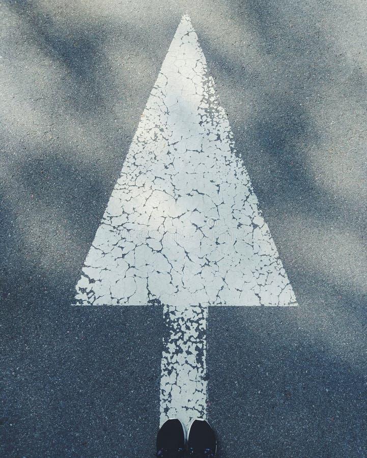 Vitt pilsymbol som dras på asfaltvägen royaltyfri bild