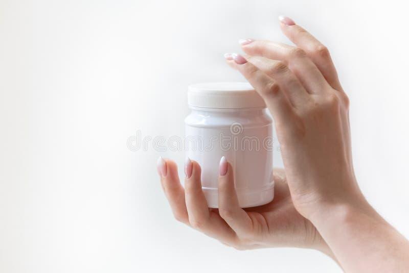 Vitt plast- kan för medicin i kvinnliga händer, medicin, första hjälpen arkivbilder