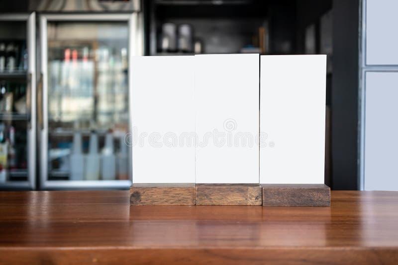 Vitt plast- menybräde på träräknaretabellen framme av kök arkivbilder