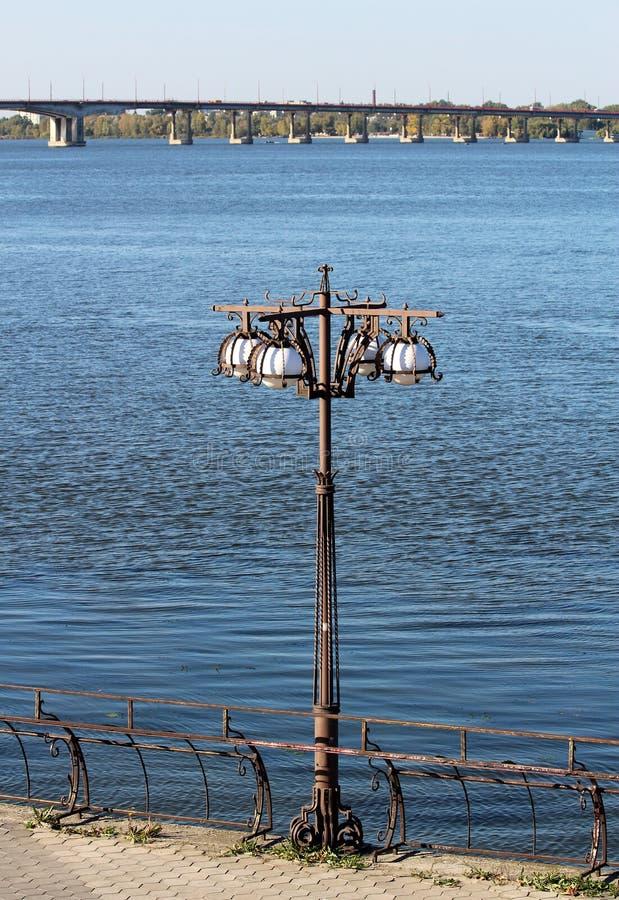 vitt plofony i metallskulptur med en lyktstolpe med en bakgrund av den blåa floden och bron arkivfoton