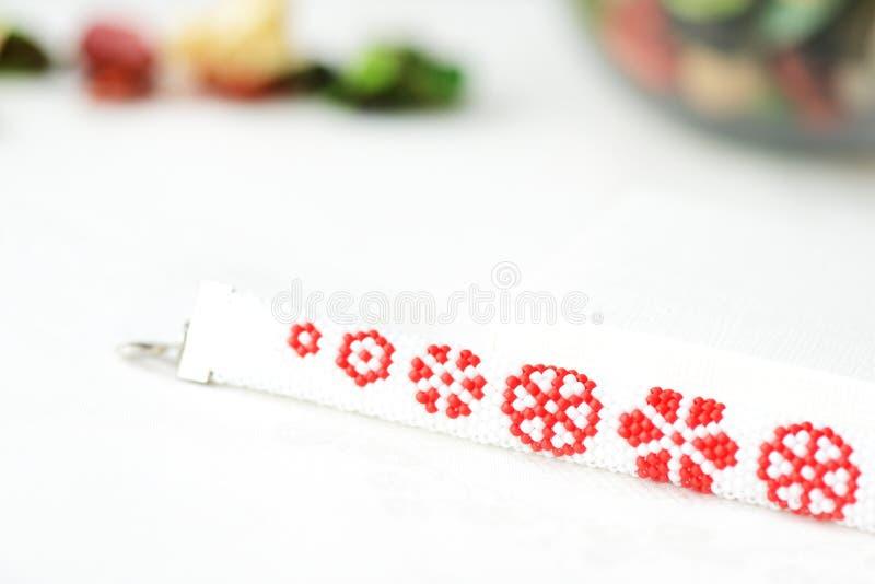 Vitt prytt med pärlor armband med det röda blommatrycket arkivbild