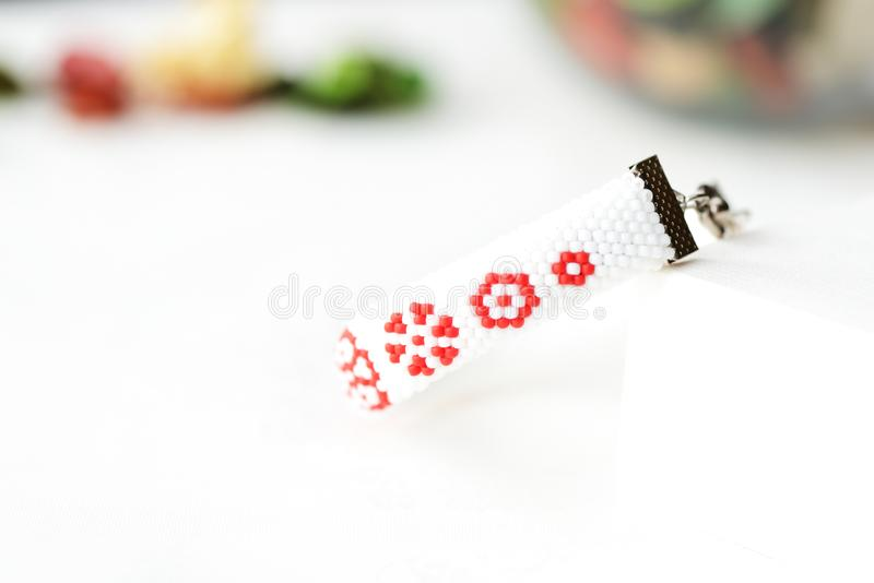 Vitt prytt med pärlor armband med det röda blommatrycket arkivfoton