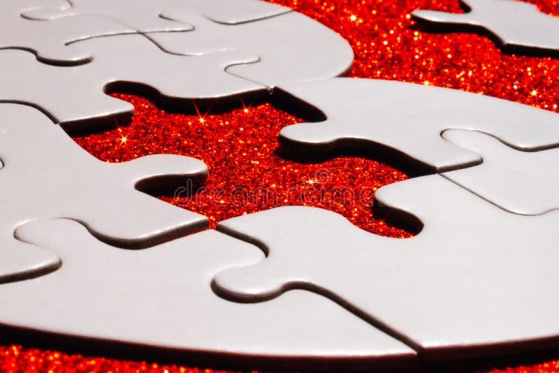 Vitt pussel på röd gnistrandebakgrund fotografering för bildbyråer