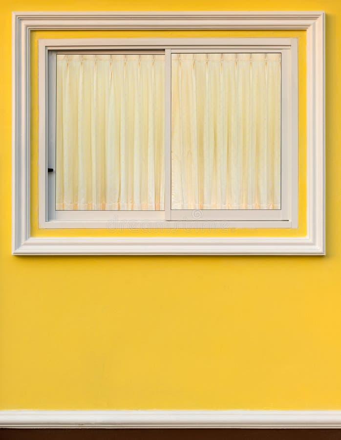 Vitt ramfönster i gul vägg med gardinen arkivfoton