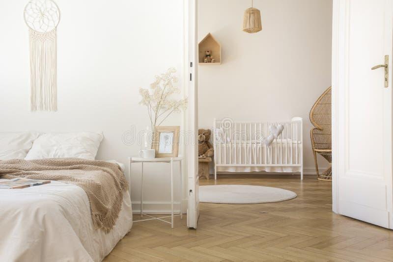 Vitt scandinavian sovrum med dörren som är öppen till barnkammaren royaltyfria bilder