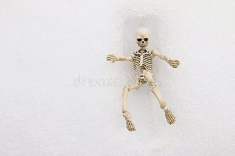 Vitt skelett- försöka att få ut ur en fyrkantig grav arkivfoton