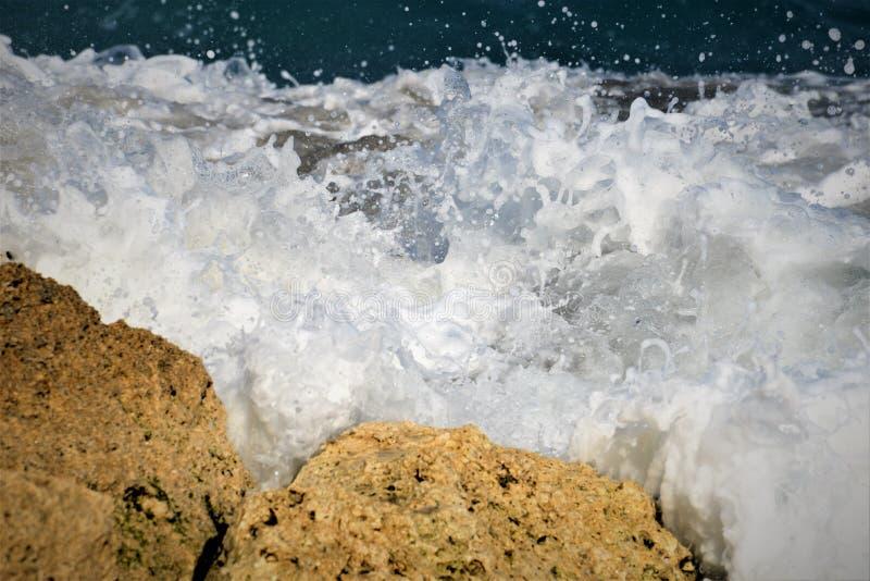 Vitt skum från havvågorna blöter vaggar av Boca Beach royaltyfri foto