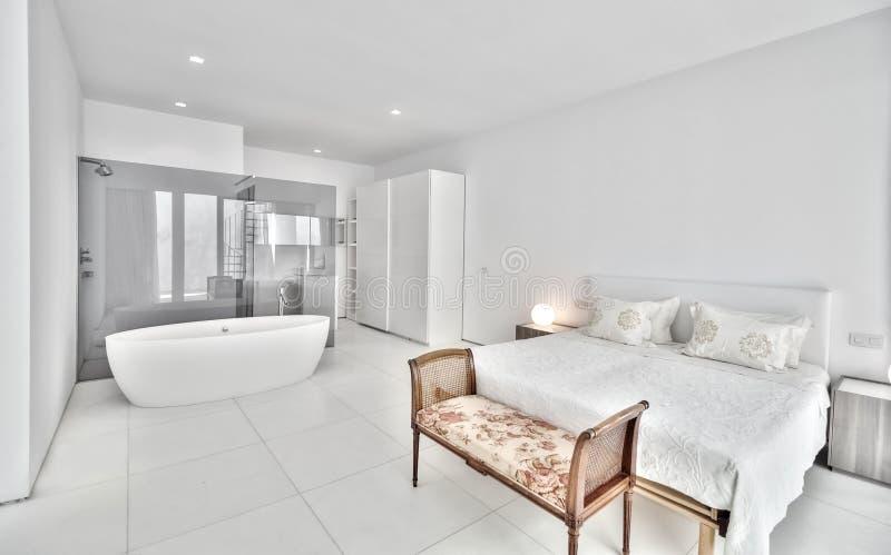 Vitt sovrum i den moderna villan royaltyfri bild