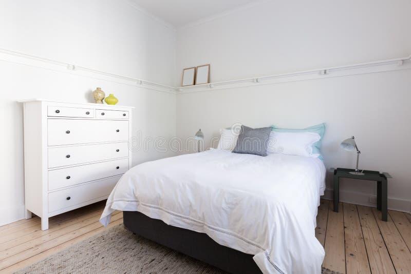 Vitt sovrum med dekoratörobjekt i strand utformade hem- apartmen royaltyfri fotografi