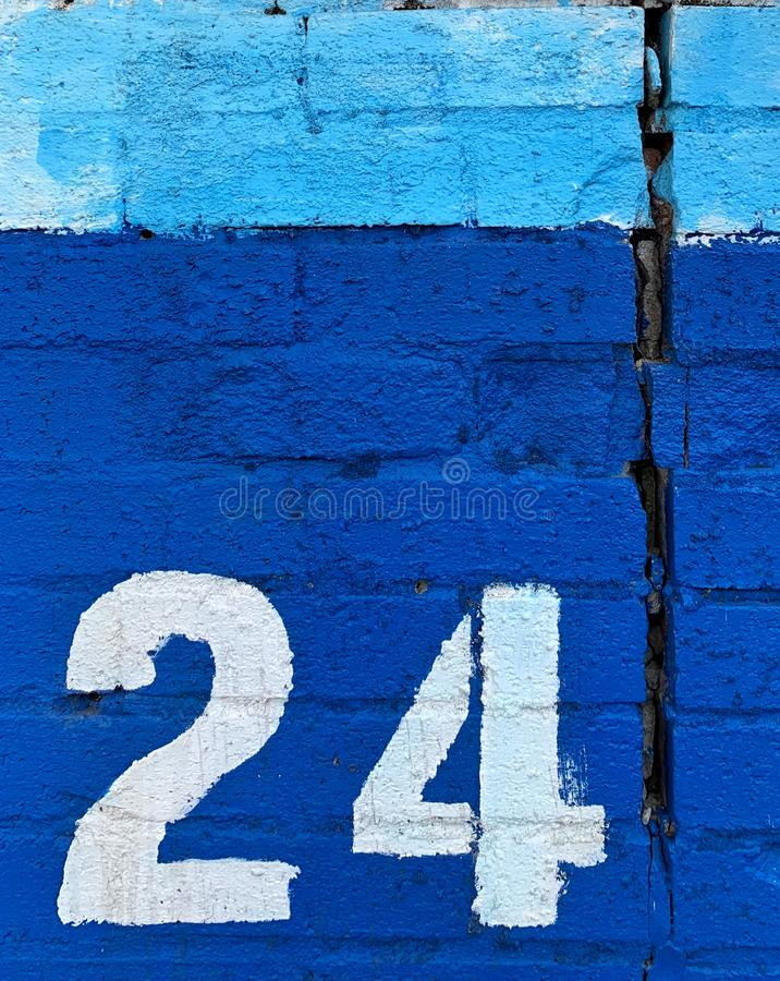 Vitt stencilerat nummer tjugofyra på väggen arkivbilder