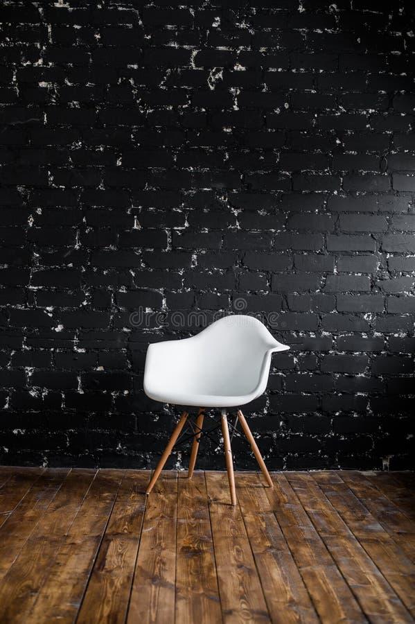 Vitt stolanseende i rum på brunt trägolv över den svarta tegelstenväggen royaltyfria bilder