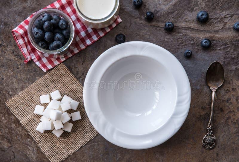 Vitt töm plattan, och skeden på stenen kritiserar bakgrund med ingredienser för glass arkivbilder