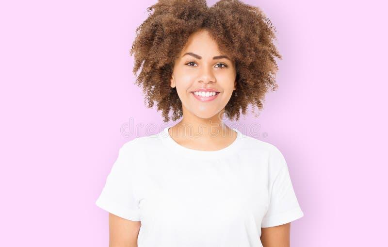 Vitt tandleende Ung afrikansk amerikankvinna med perfekt hudomsorg och lockigt afro hår som isoleras på rosa bakgrund _ royaltyfri foto