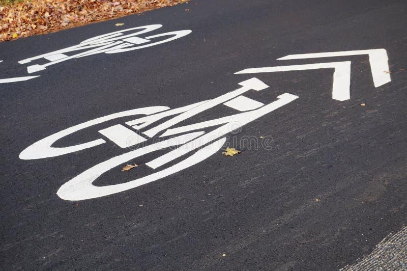 Vitt tecken för cykelgränd som markeras på vägasfalt royaltyfri bild