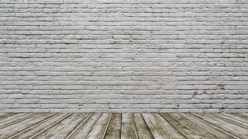 Vitt tegelstenvägg och trägolv arkivbild