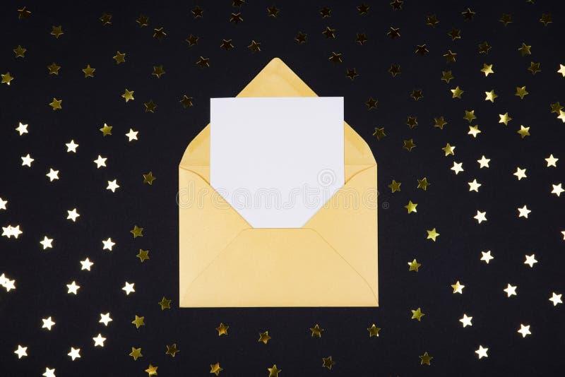 Vitt tomt kort i öppnat guld- färgkuvert på svart bakgrund som dekoreras med stjärnakonfettier fotografering för bildbyråer