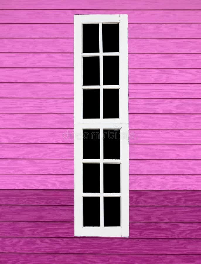 Vitt trä för långt fönster i den rosa väggen arkivbild