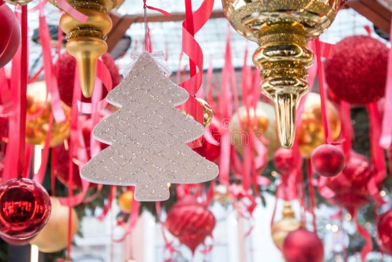 Vitt träd för jul som hänger på röda band i den ganska kiosket för seminarium och försäljning handcrafted xmas-gåvor utomhus arkivfoton