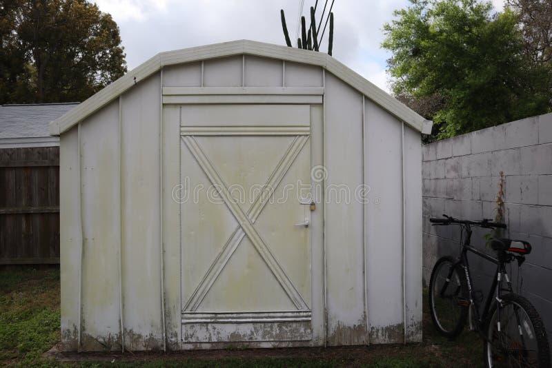 Vitt trädgårdskjul cykel på staketet arkivfoto