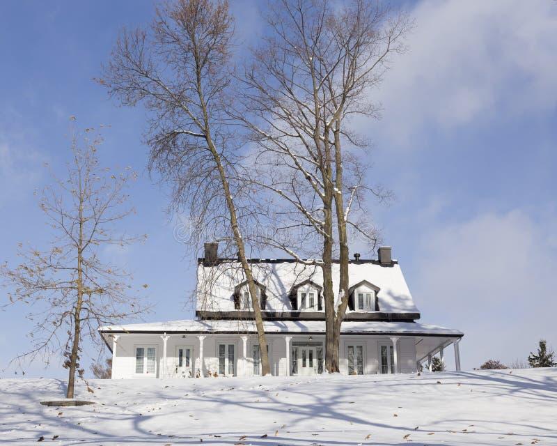 Vitt trälandshus med det snöig svarta taket i vinterlandskap royaltyfria foton