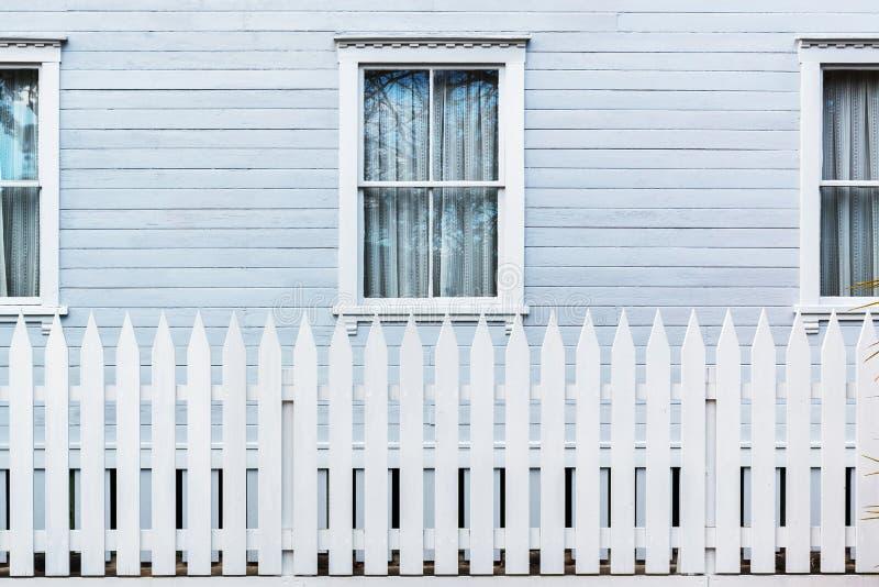 Vitt trästaket för landsstil med fönster av huset royaltyfri bild