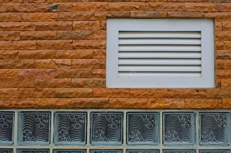 Vitt uttag på tegelstenväggen med ljusa glass kvarter royaltyfri foto