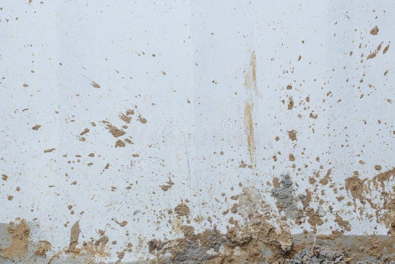 Vitt väggcement som är smutsigt med lerigt plaska arkivbild
