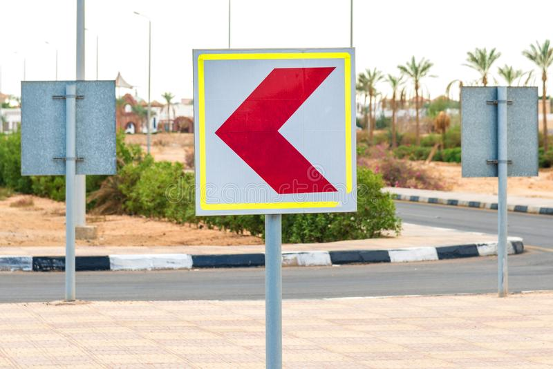 Vitt vägmärke för fyrkant med en röd pil som vänds till vänstersidan Horisontal inrama royaltyfri fotografi