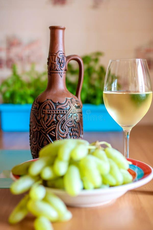 Vitt vin i exponeringsglas, dekorativ strid och en grupp av isolerade vita druvor royaltyfri foto