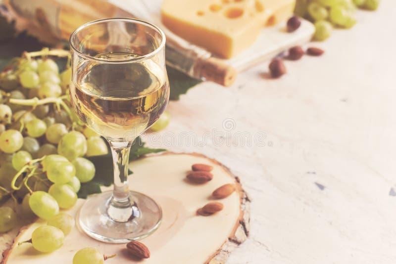 Vitt vin i exponeringsglaset på bakgrunden av druvan och ost fotografering för bildbyråer