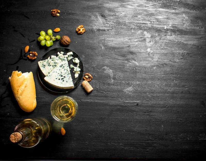 Vitt vin med fransk ädelost och muttrar royaltyfria foton