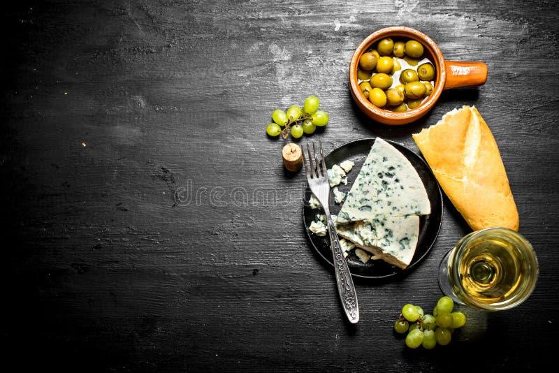 Vitt vin med välsmakande ost och smakliga oliv arkivfoton