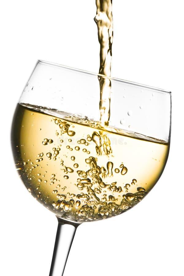 Vitt vin som häller in i exponeringsglas, vippade på med utrymme för text royaltyfri foto