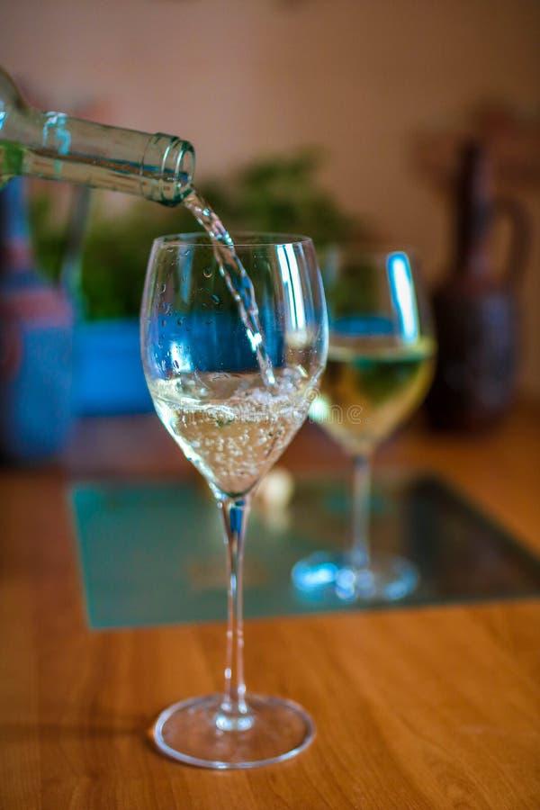 Vitt vin som in häller till ett exponeringsglas från en flaska arkivbilder