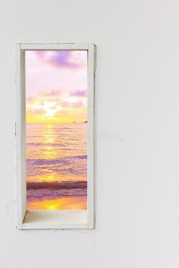 Vitt wood väggfönster med sikt för solnedgånghavsstrand arkivbilder