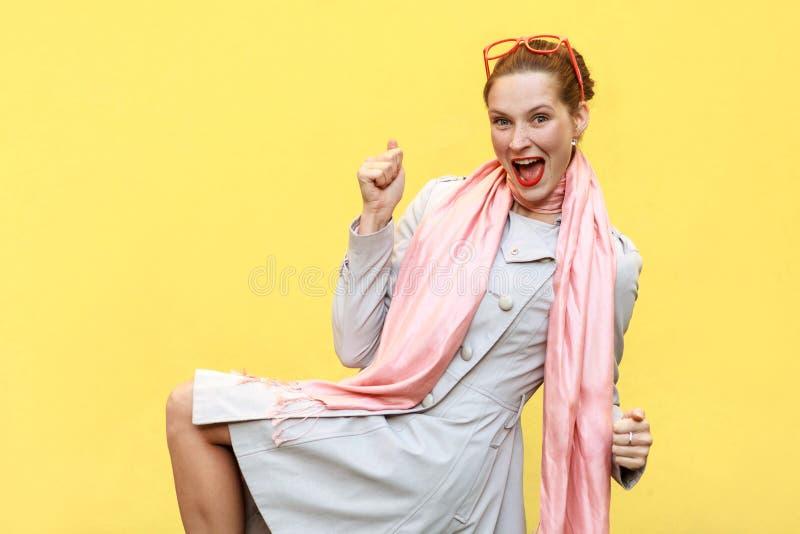Vittoria! Esultanza della donna dello zenzero per il suo successo Isolato su giallo immagine stock