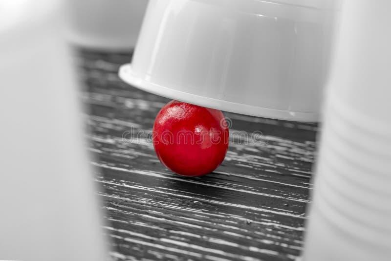 Vittoria rossa della palla sotto una tazza bianca nel gioco delle tazze fotografie stock